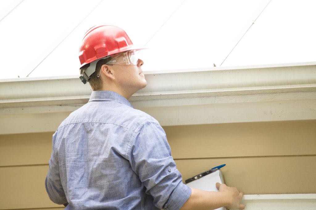 Contractor inspecting metal roofing